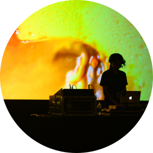 DJ onstage with yellow psychedelic projection behind