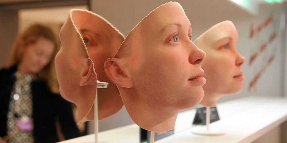 mask-like faces made of silicon hung on a mirrored wall