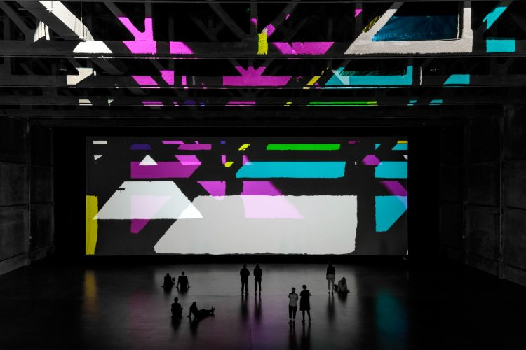 large room with multicolored projections on the walls and people sitting on the floor